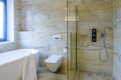 Koupelna je obložena přírodním leštěným mramorem. Vzhledem kvýrazné kresbě obkladu avzájmu zachování designové jednoty ačistoty je vybavení koupelny striktně minimalistické