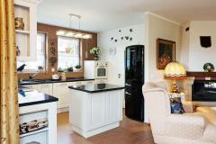 Kuchyň vpřízemí odděluje odobývacího pokoje  malý varný ostrůvek. Hned vedle černé chladničky jsou dveře dospíže