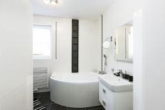 Obě koupelny jsou vybaveny rohovou vanou isprchou. Bílý obklad je nadčasový aopticky prosvětluje azvětšuje prostor