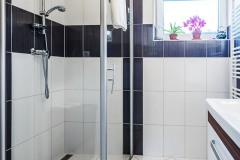 Prostorný sprchový kout a skříňka s umyvadlem v koupelně. Světlé dlaždice na zdech využívají kontrastu s tmavým odstínem