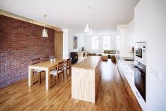 Odstraněním příčky vznikl velkorysý prostor zahrnující kuchyň, jídelní kout, relaxační respirium aobývací pokoj