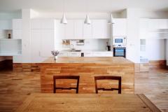 Jídelní akuchyňská zóna jsou vybaveny zakázkovým nábytkem, který navrhli architekti ze studia AEIOU