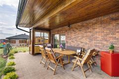 Terasa s venkovním nábytkem je chráněna přesahem střechy před deštěm i sluncem. Skleněná výplň z boční strany je instalována dodatečně a chrání terasu před větrem