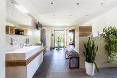 Velkorysá koupelna zahrnuje sprchu, vanu, saunu i kondiční stroj a umožňuje přímý výstup do zahrady