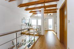 Po otevřeném halovém schodišti se dostanete nahoru na galerii lemovanou krásným nerezovým zábradlím. Odtud lze přehlédnout část hlavního obytného prostoru i prostor krovu. Z galerie se vchází do jednotlivých místností v podkroví