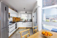 Jídelní část se stolem a kuchyňská sekce jsou od ostatních částí hlavního prostoru odděleny dvěma schody, takže nejsou ve stejné rovině. Prostor kuchyně i jídelny akcentuje světlé tóny a přírodní dřevo