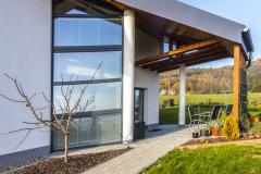 Veškeré zahradní komunikace i prostor pro terasu jsou vydlážděny betonovými venkovními dlaždicemi. Nalevo před terasou vidíte pěkný detail prosklené stěny