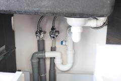 Vodovodní instalace se mohou vést např. před omítkou (zde pod kuchyňskou linkou)