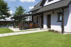 Zastřešená pergola je orientována dovnitřní části zahrady asladěna sdomem. Dřevěné laťové rošty atmavá lazura připomínají japonský styl