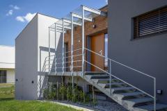 Jemný industriální prvek vstupního schodiště oživuje jednoduché tvary stavby