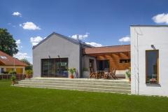 Dvě hmoty odlišené barevností fasády itvarem střechy spojuje dojednoho objektu komunikační krček obložený dřevem. Vnější rozdílnost domu se propisuje dointeriéru azdůrazňuje rozdílnost dvou obytných zón – intimní aspolečenské. Záměrem autorky projektu, architektky Heleny Paz, bylo navrhnout zvnějšku izevnitř srozumitelný dům