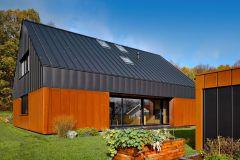 Kompaktní fasáda jednoduchého domu je členěna vertikálními falcovanými spoji cortenového a černého plechu. Barevný kontrast doplňují prosklené plochy