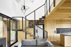 Ústřední společná obývací část je otevřená nejen do stran, ale i nahoru do podkroví. Nejsou tu žádné zdi, vymezují ji prosklené stěny, stropy a vestavěný nábytek, který spolu s dveřmi a obklady z téhož materiálu vytváří jednolitou, čistě funkčně členěnou plochu