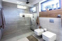 Sluncem prosvětlená koupelna kombinuje velkoformátový bezespárový obklad adlažbu sdřevěným obkladem. Sprchový kout je oddělen minimalistickou skleněnou stěnou.