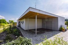 Zastřešené stání pro dva automobily asklad. Sklad varchitektonické koncepci domu rozšiřuje jižní fasádu, která spolu sterasou  a stěnou na východní straně vytváří atrium.