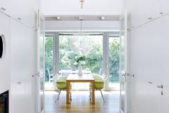 Minimalismus a bílá barva povýšily halu na elegantní prostor. Dvoukřídlými dveřmi lze vejít do společného obytného prostoru a odtud opět na protější straně francouzským oknem na terasu. Otevřením obou dveří se opticky i skutečně zvětšuje vnitřní obytný prostor domu