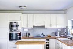 """Kuchyňskou linku vtradičním stylu oživuje pracovní deska zdřevěné spárovky vpřírodním odstínu. Podlaha má """"kouřový"""" nádech zvýrazňující strukturu dřeva"""