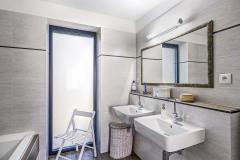 Také koupelna se světlými šedavými obklady ahnědou dlažbou ctí barevnou linii interiéru domu