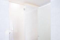 Interiér koupelny umístěné vkubické vestavbě vzadní části přízemí domu. Nahoře je vidět střešní okno, které dovestavby přivádí denní světlo