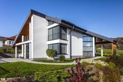 Zvolený tvar domu citlivě pracuje s tvarem svažitého pozemku i jeho orientací. Hmotová konfigurace domu je tradiční, ale nepostrádá některé progresivní architektonické prvky